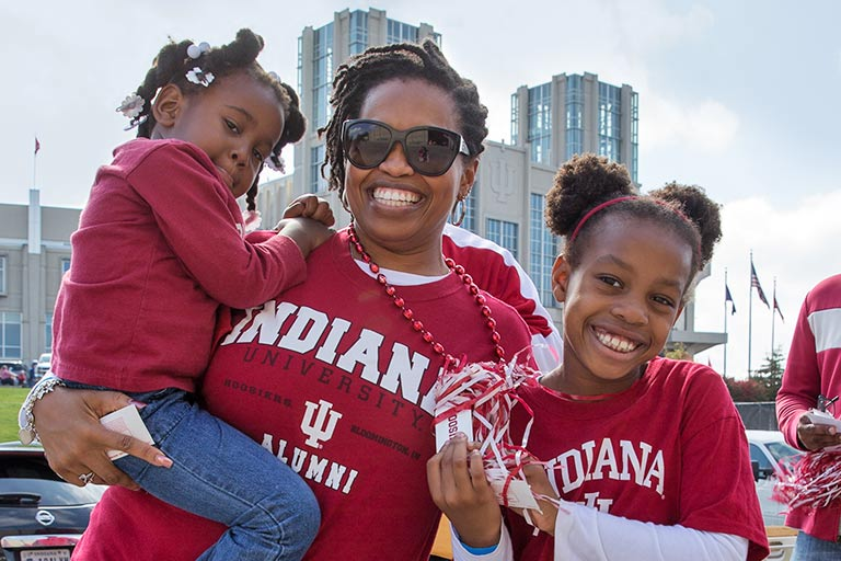 An African American woman wearing an IU shirt smiles while holding a small child and standing next to another.