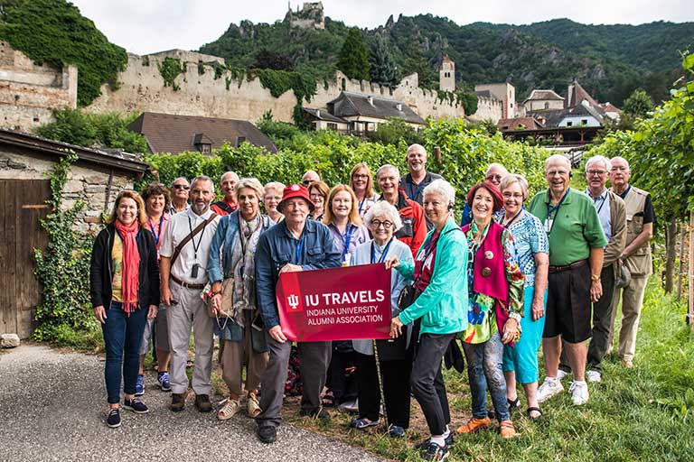 A group of people holding an IU Travels sign stand in front of a European village