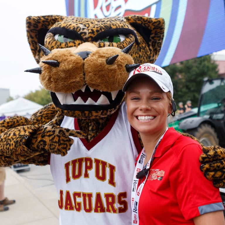 Jawz, the IUPUI jaguar mascot, poses with a woman in a red shirt and ball cap