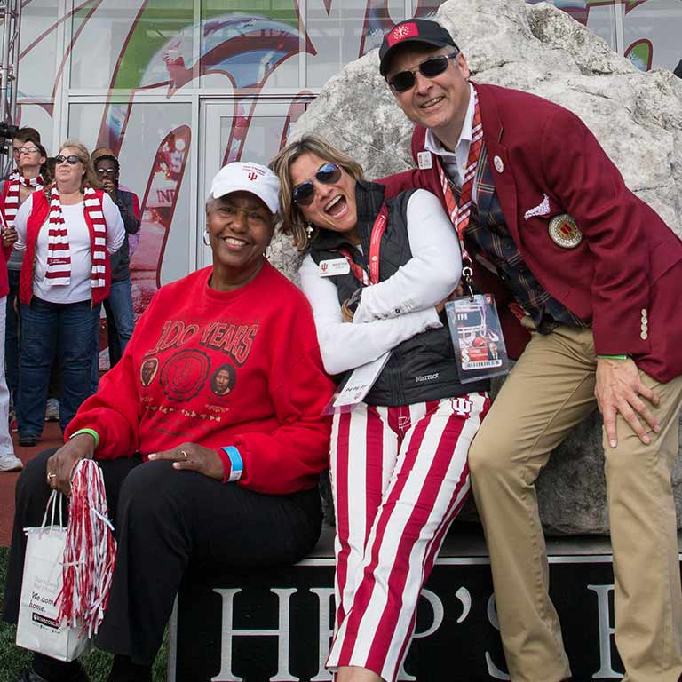 Three people stand in front of the rock in IU Memorial Stadium. The woman in the middle is wearing candy stripe pants