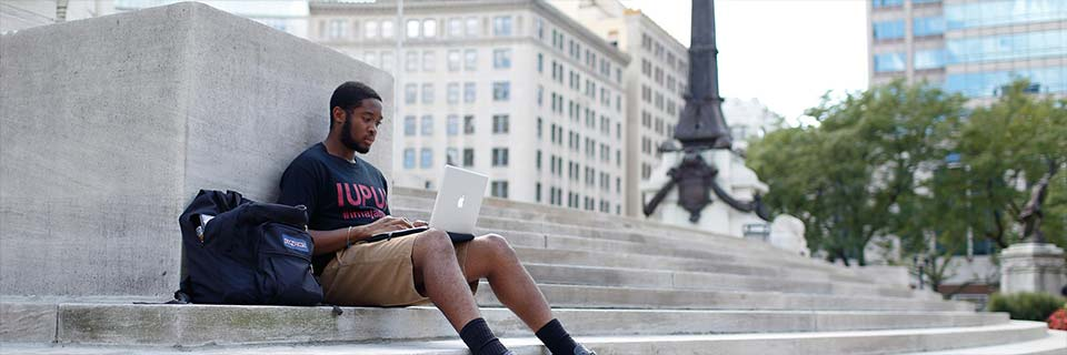 An African American man in a black IUPUI T-shirt sits on cement steps with a computer