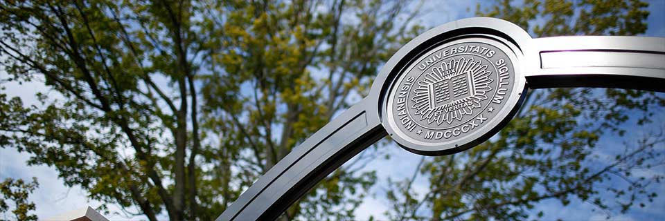 Indiana University seal on a metal arch in front of a blue sky