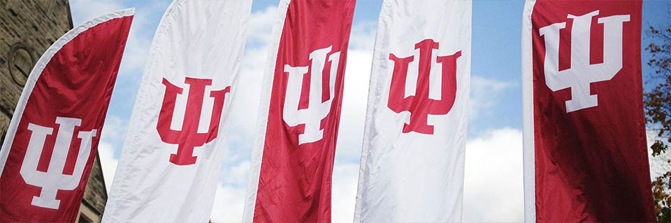 A row of red and white outdoor banners with the IU trident
