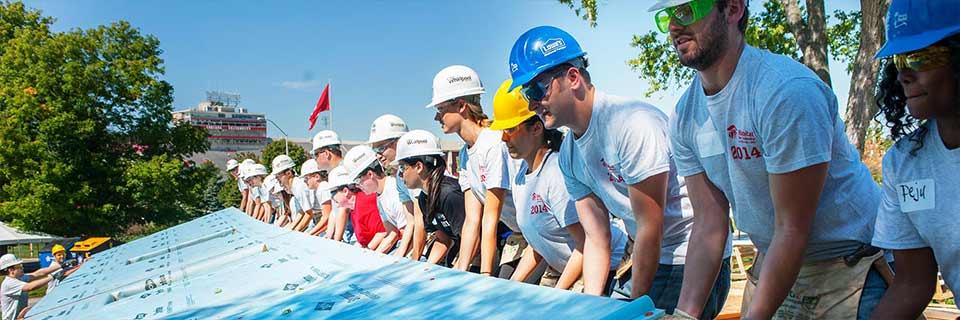 A group of people wearing hard hats work together to raise a blue wall