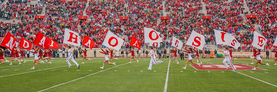 IU cheerleaders run out on to the football field holding letters that spell Indiana Hoosiers