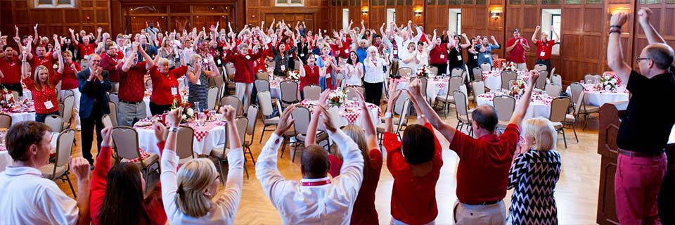 A large group of alumni stand in a circle in a wood paneled room doing the fist and blades.