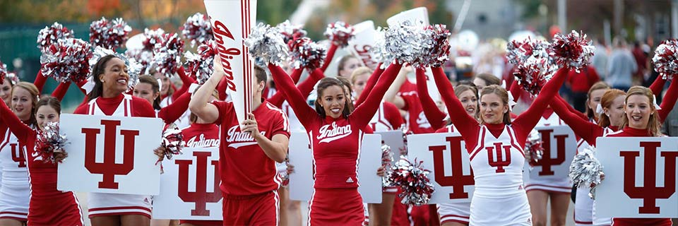 IU cheerleaders in uniform cheer in a line