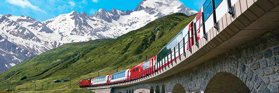 A red train crosses a stone bridge in front of green and snow covered mountains