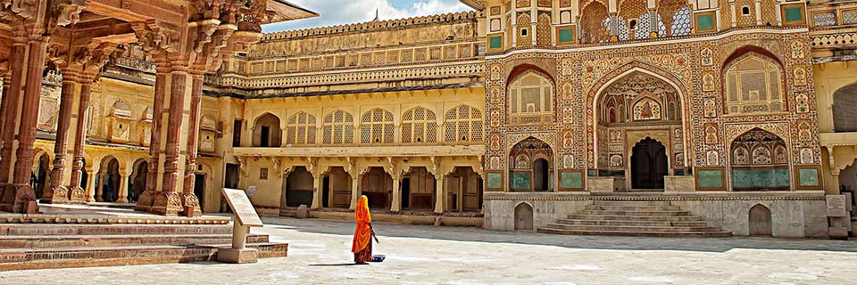 A woman wearing an orange hijab stands in the courtyard of an extravagantly decorated building in India