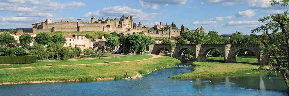 A scenic view of the French town Carcassonne, which is located on a green hilltop.