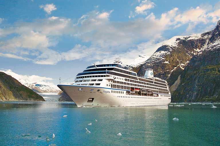 A cruise ship sails between snow-capped mountains