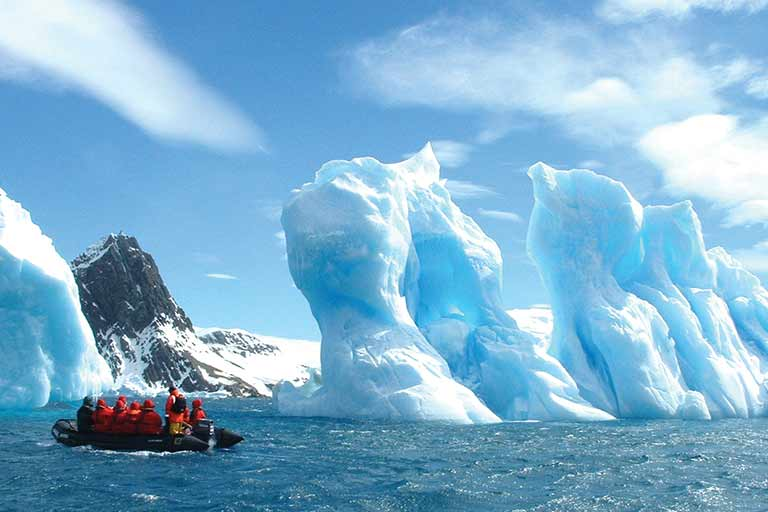 An inflatable boat floats between towering ice floes