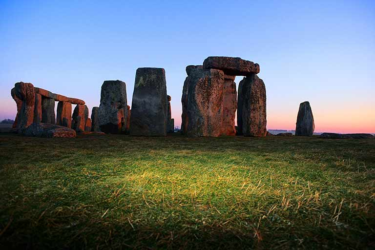 Looking across green grass at Stonehenge at sunset