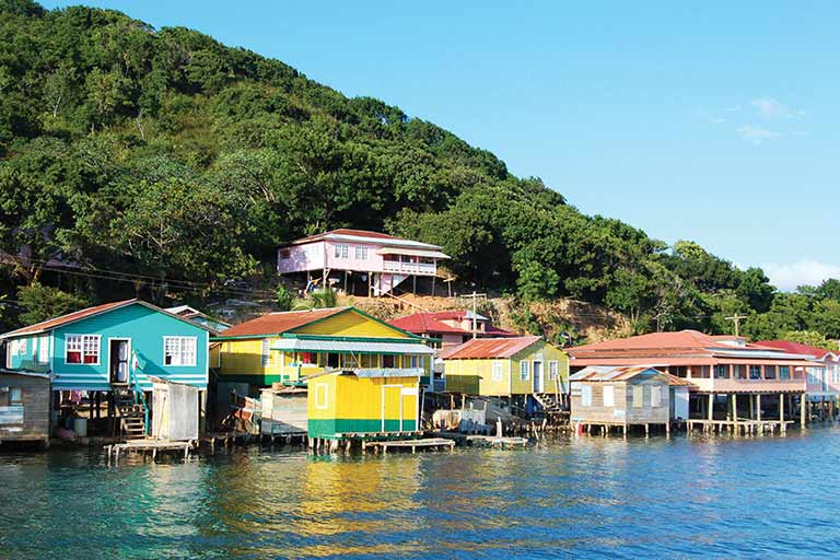 Blue, yellow, and pink houses stand on stilts in water