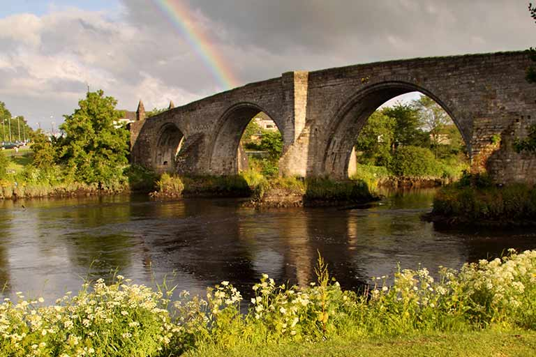 Looking over a river at a stone bridge. A rainbow is in the sky.